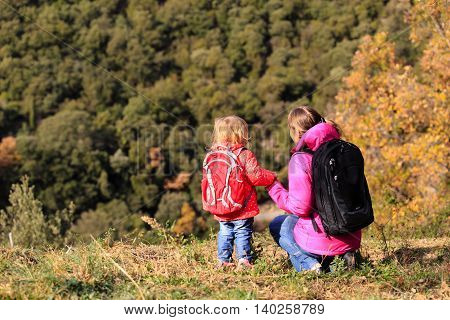mother and little daughter travel in autumn mountains