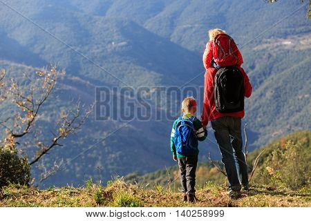 father with two kids travel in scenic mountains
