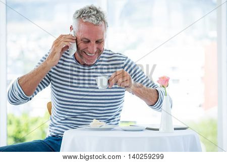 Smiling mature man talking on phone while having coffee at restaurant