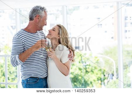 Smiling romantic mature couple with wine glasses while sitting at restaurant