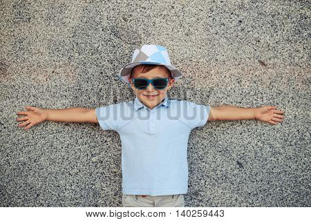 Small boy is standing near the wall in the street with his arms spread to the sides and smiling