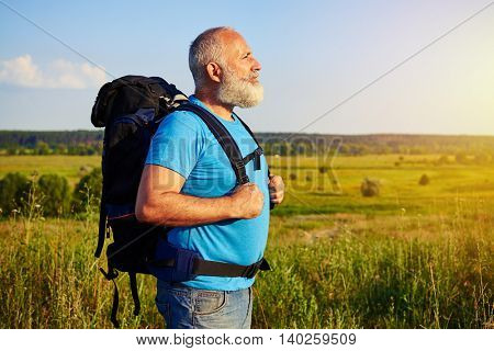 Side view of healthy aged man carrying a rucksack against sunlit field background