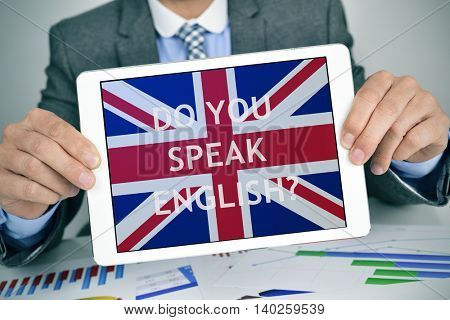 closeup of a young caucasian businessman at his office desk full of charts showing a tablet computer with the question do you speak English? and the flag of United Kingdom in its screen