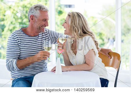 Smiling mature couple discussing while having wine at restaurant