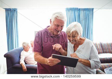 Smiling senior people looking at a digital tablet