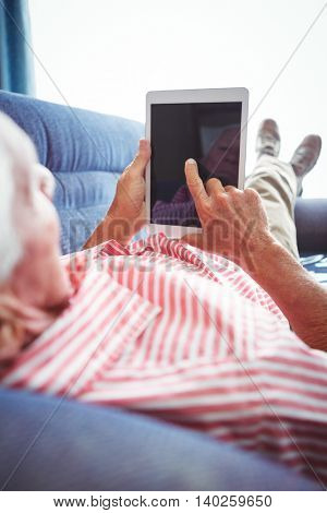 Lying on a couch senior man touching digital tablet on a sunny day