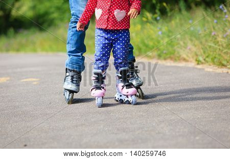 father teaching little daugther to roller skate in summer