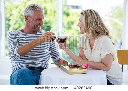 Smiling mature couple toasting red wine while sitting at restaurant