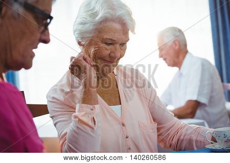 Senior smiling woman with a cup of coffee in a retirement home