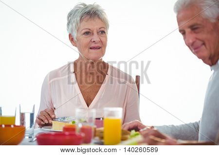 Senior women during lunch on a white background