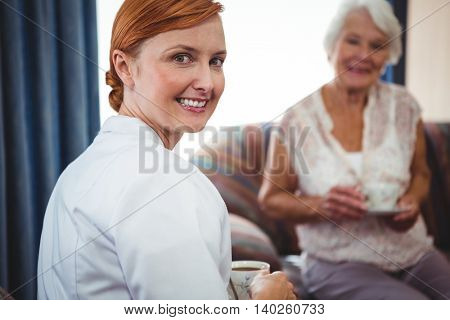 Portrait of a nurse looking behind her with an senior person beind her