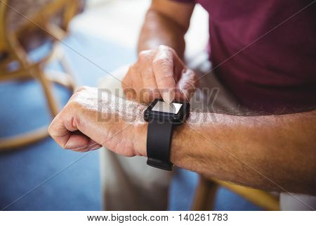 Senior man using a smart watch in a retirement home