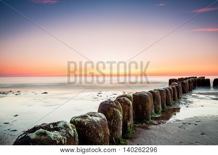 Sunset at Baltic sea view on old breakwater piles.