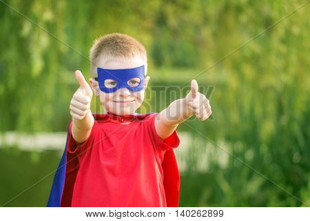 Kid in superhero costume showing thumbs up. The winner and success concept.