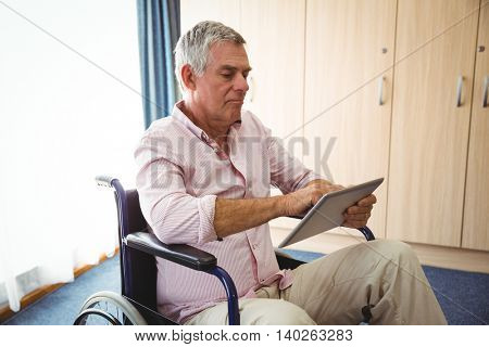 Senior using a tablet in a wheelchair in a retirement home