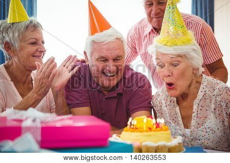 Senior woman blow on birthday cake during a birthday party