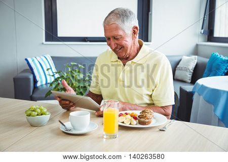 Senior man using a digital tablet in a retirement home
