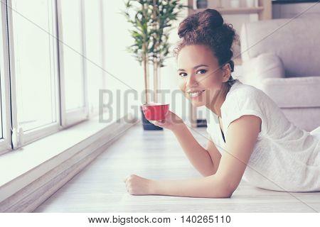 Beautiful African American girl with coffee lying on floor