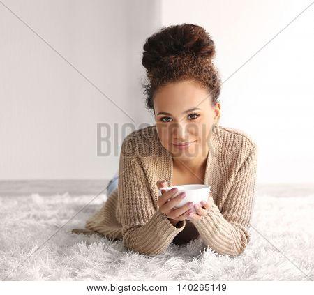 Beautiful African American girl with coffee lying on carpet