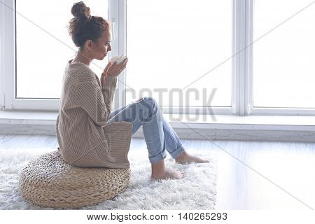 Beautiful African American girl drinking coffee at home