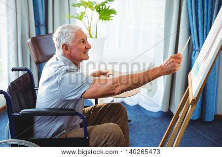 Senior man using brush and easel in a retirement home