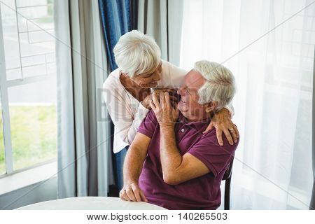 Senior couple hugging each other in a retirement home