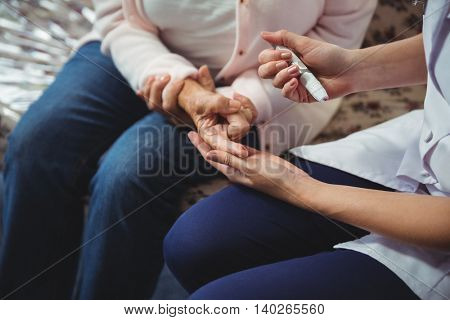 Nurse helping senior woman with diabetes in a retirement home