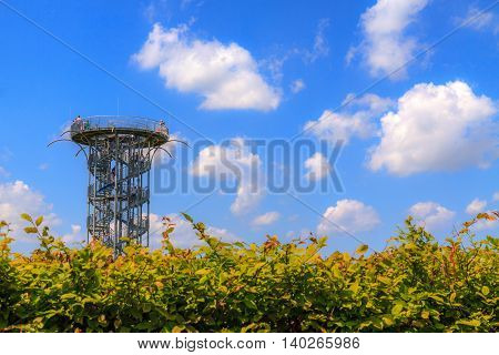 Metal tower on garden with blue sky.