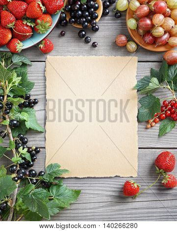Healthy Berries background. Old paper with fresh strawberry currants and gooseberry on wooden table. Copy space top view high resolution product.