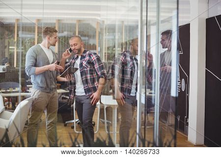 Colleague discussing while businessman talking on phone in creative office