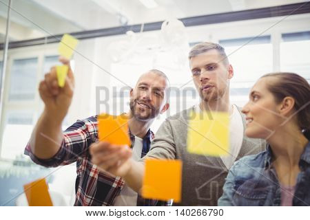 Young business people sticking adhesive notes on glass window in creative office