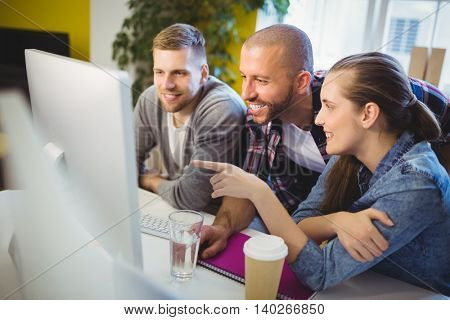 Businesswoman pointing on computer while discussing with colleagues at desk in creative office