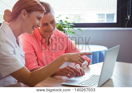 Nurse and senior woman using a laptop in a retirement home