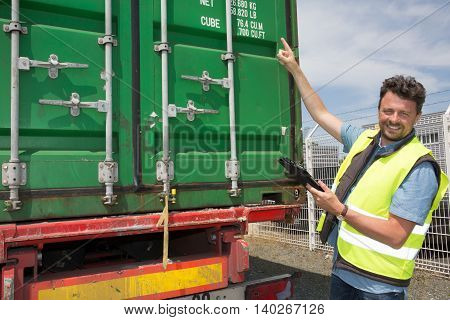 Portrait Of Delivery Man Smiling Using Digital Tablet By Truck