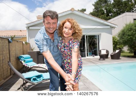 Happy Couple Sitting In From Of Their New Home With Swimming Pool