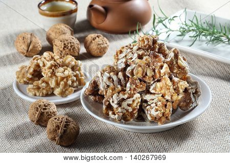 Candy of walnuts with tea in Chinese style on white plate