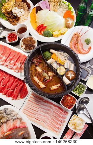 A special hot pot in Chinese style with beef pork seafood mushroom vegetables shrimps and herbs