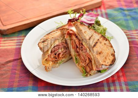 Sandwiches of bacon and herbs on white plate on the table