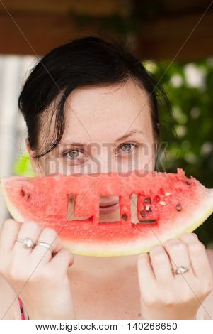 A cute girl with a piece of watermelon in his hand the inscription carved in the pulp of the fruit