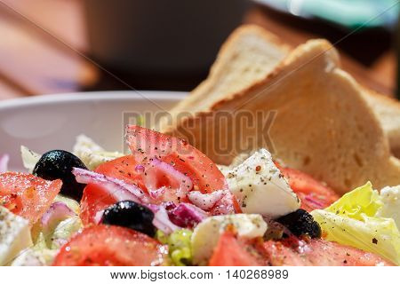 Fresh greek salad with grilled bread for healthy lunch.
