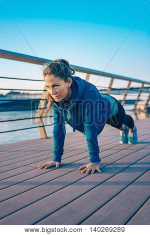 Woman doing plank on riverside, toned image, vertical image