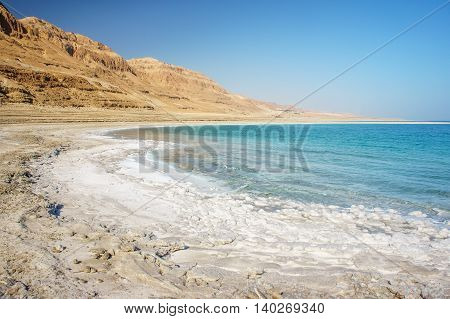 View of Dead Sea coastline with white salt beach and blue mineral water at sunny day in Ein Bokek, Israel