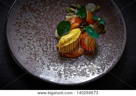 Fish School Pumpkin icecream persimmon melon with fried peanut and green pennywort in plate in black background