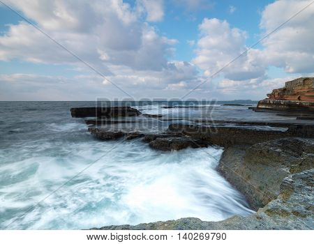 long exposure shot to sea side with rocks and waves
