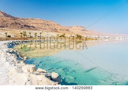 View of Dead Sea coastline with white beach made of salt and mountains at sunny day in Israel