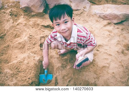 Top View. Adorable Asian Boy Has Fun Digging In The Sand On A Summer Day. Vintage Tone. Child Smilin