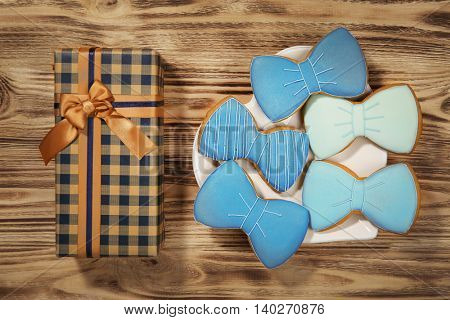 Happy Father's Day concept. Tasty cookies and gift box on wooden background