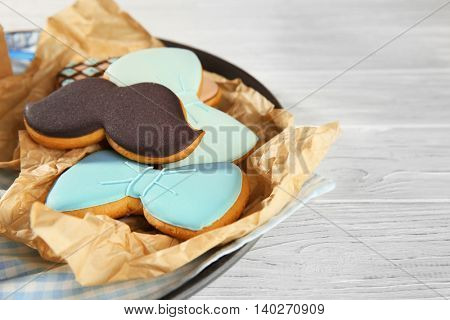 Happy Father's Day concept. Plate with tasty cookies on wooden background