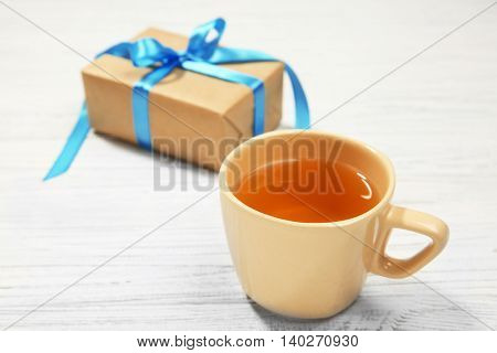 Cup of tea and gift box on wooden background