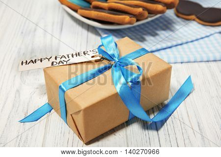 Happy Father's Day concept. Plate with tasty cookies and gift box on wooden background